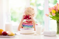 Child eating breakfast. Kid with milk and cereal. Child having breakfast. Kid drinking milk and eating cereal with fruit. Little boy at white dining table in royalty free stock photos