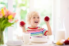 Child eating breakfast. Kid with milk and cereal. Child having breakfast. Kid drinking milk and eating cereal with fruit. Little boy at white dining table in stock photography