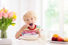 Child eating breakfast. Kid with milk and cereal. Child having breakfast. Kid drinking milk and eating cereal with fruit. Little boy at white dining table in stock photo