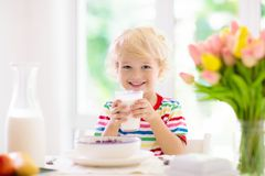 Child eating breakfast. Kid with milk and cereal. Child having breakfast. Kid drinking milk and eating cereal with fruit. Little boy at white dining table in stock photos