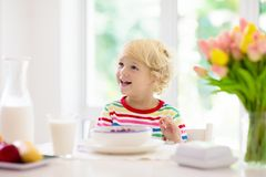 Child eating breakfast. Kid with milk and cereal stock images