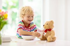 Child eating breakfast. Kid with milk and cereal. Child having breakfast. Kid feeding teddy bear toy, drinking milk and eating cereal with fruit. Little boy at stock image