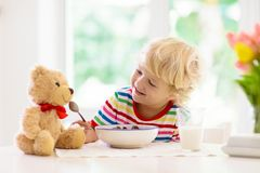 Child eating breakfast. Kid with milk and cereal stock photos