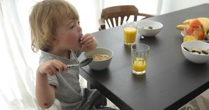 Child eat breakfast. Child is having breakfast and looking at camera and smiling at the table in room stock video