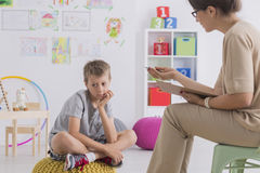 Child having conversation with psychotherapist. Bored child sitting on pouf while having conersation with psychotherapist Stock Photos