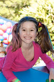 Child having fun. Portrait of excited little girl with cute pony tails and hair accessories, smiling brightly Stock Photo