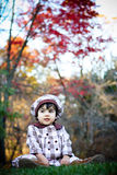 Child having fun. Two year old sitting on grasses with beautiful fall colors in the background Stock Image