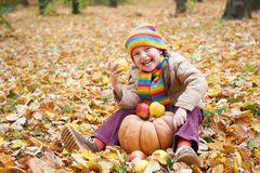 Child having fun with apple and pumpkin in forest, sit on autumn leaves background, fall season Royalty Free Stock Photos
