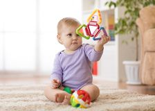 Adorable baby girl playing with educational toys in nursery. Royalty Free Stock Photo