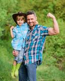 Child having fun cowboy dad. Rustic family. Growing cute cowboy. Small helper in garden. Little boy and father in nature royalty free stock photography
