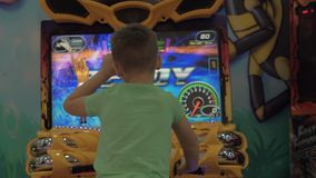 Child having fun with motorbike racing simulator. Antalya, Turkey - November 11, 2017: Back view of the boy with model release playing motorcycle racing stock video footage