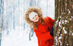 Child having fun outdoors with snowball in winter. Snowy forest Royalty Free Stock Photo