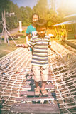 Child having fun at playground, mother near by. Happy asian fami Royalty Free Stock Image