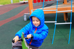 Child having fun at playground riding on the spring horse Royalty Free Stock Photos