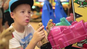 Child having fun with shooter attraction. Boy playing on shooter attraction in indoor amusement park and he is dissatisfied with the result stock video footage