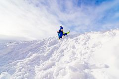 Child having fun at snowy hill. Sliding down. Winter fun Stock Images