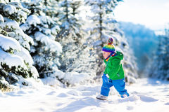 Child having fun in snowy winter park Stock Photo