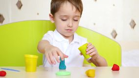 Child having fun at the table, playing colorful clay modeling or dough for games stock video