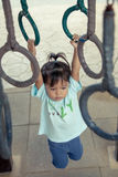 Child having fun to hanging on bar in playground. In vintage filter Stock Image