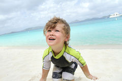 Child having Fun on Tropical Beach near Ocean Stock Photos