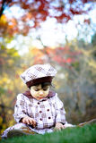Child having fun2. Two year old sitting on grasses with beautiful fall colors in the background Stock Photography