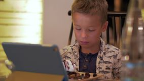 Child having meal and watching touch pad in cafe. Boy eating dessert in cafe and watching cartoons on tablet computer stock footage