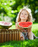 Child having picnic in spring park. Happy smiling child eating watermelon outdoors in spring park Stock Photo