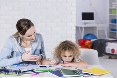 Child having problem with concentration. Mother and child having problem with concentration while doing homework Royalty Free Stock Photo