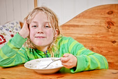 Child having snack. Young girl having snack at the table Royalty Free Stock Photo