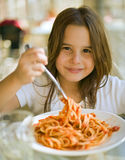 Child having spaghetti. Young girl eating spaghetti in restaurant Stock Image