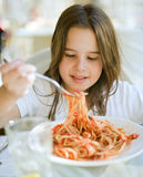 Child having spaghetti. Young girl eating spaghetti in restaurant Stock Images