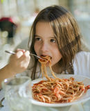 Child having spaghetti. Young girl eating spaghetti in restaurant Royalty Free Stock Photography