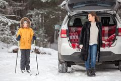 Child having sport activity in forest and mother standing in fur coat near back of suv. Winter season Stock Images