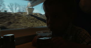 Child having tea and looking out window in moving. Little boy traveling by train. He having tea and looking out the window. Train going under the bridge stock video footage