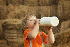 Child on a haystack drink milk Stock Photo