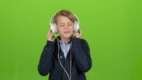 Child in the headphones is listening to music. Green screen stock video