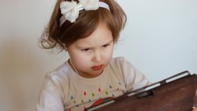 Child in headphones looks at the screen monitor Tablet PC. A little cute girl looking tv, video,cartoon or playing the. Game application stock video footage
