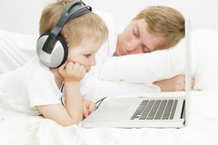 Child in headsets with computer while father is asleep Royalty Free Stock Photo