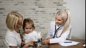 Child Health Examination. Young mother and her little pretty daughter visit family doctor. Friendly ENT Pediatrician. Doctor using phonendoscope and a toy stock video