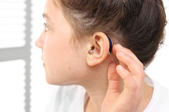 A child with a hearing aid. The girl assumes hearing aid Stock Photo