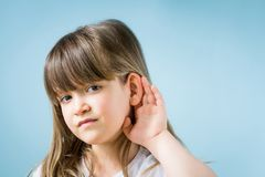 Toddler girl with hearing problem on light blue background. Close up, copy space. Child with hearing problem on blue background. Hearing loss in childhood royalty free stock images