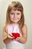 Child and heart. Red heart in hands and slightly blurred child face ir background Royalty Free Stock Images