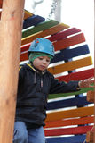 Child with helmet climbing at playground Royalty Free Stock Photography