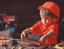 Child in helmet cute playing as builder or repairer, repairing or handcrafting. Handcrafting concept. Kid boy hammered. Nail into wooden board. Toddler on busy royalty free stock photo