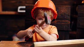 Child in helmet cute playing as builder or repairer, repairing or handcrafting. Kid boy hammering nail into wooden board. Toddler on busy face plays at home in stock footage