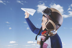 Child with helmet and paper plane Stock Photo