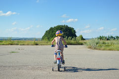 Child in a helmet riding bike on summer blue sky Royalty Free Stock Images