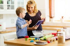 Child helping mother bake cookies Royalty Free Stock Photography