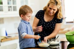 Child helping mother bake cookies Stock Photo