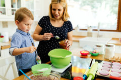 Child helping mother bake cookies Royalty Free Stock Photos